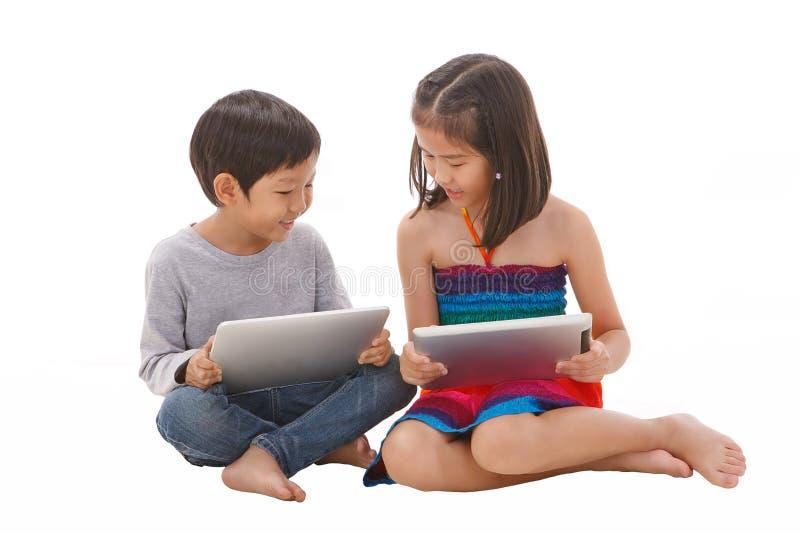 Chłopiec i dziewczyna używa pastylkę fotografia stock