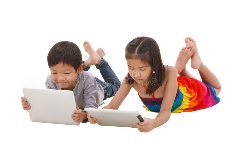 Chłopiec i dziewczyna używa pastylkę zdjęcia royalty free