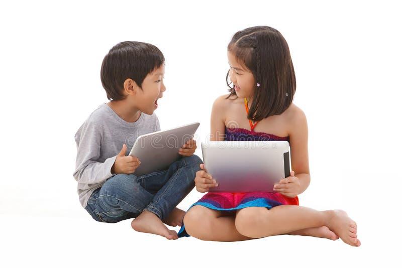 Chłopiec i dziewczyna używa pastylkę fotografia royalty free