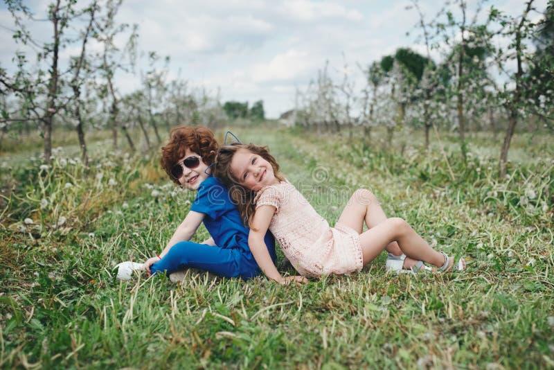 Chłopiec i dziewczyna w kwitnienie ogródzie zdjęcie stock