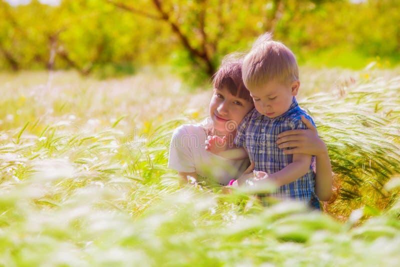 Chłopiec i dziewczyna w lata polu z kwiatami zdjęcia stock
