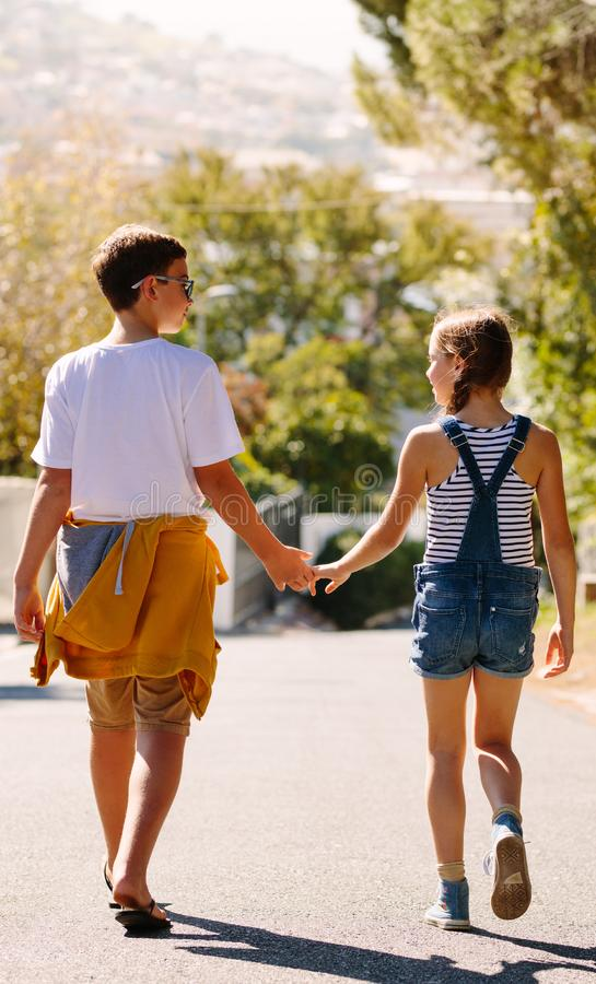 Chłopiec i dziewczyna w miłości chodzi na ulicznych mienie rękach obrazy royalty free