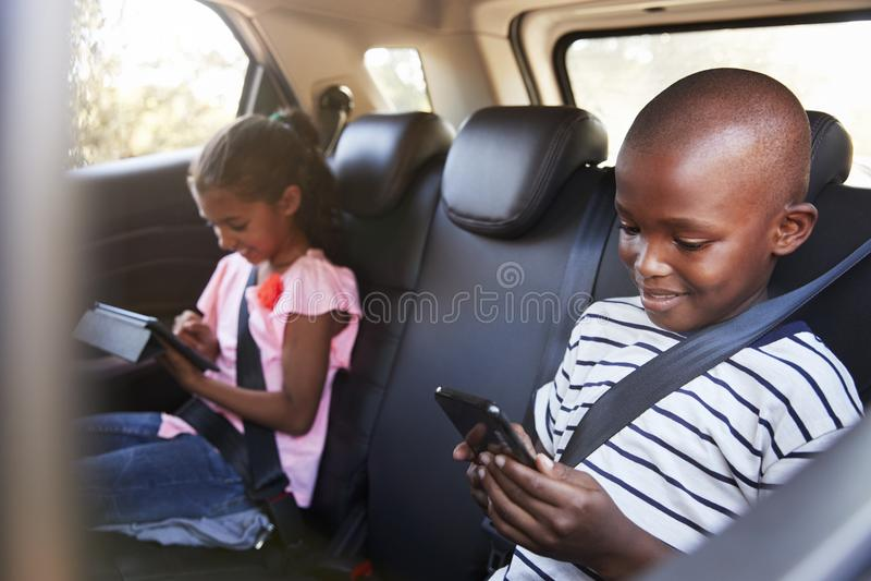 Chłopiec i dziewczyna w samochodowym używa smartphone na wycieczce i pastylce zdjęcia stock