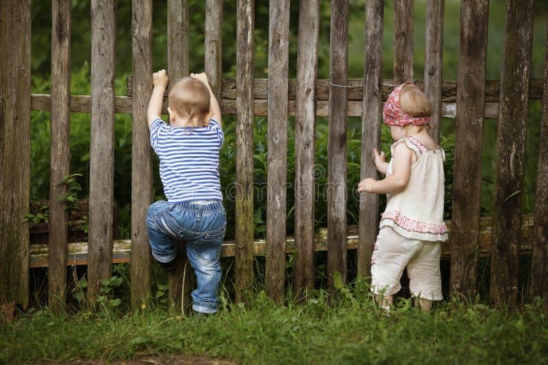 Chłopiec i dziewczyna wspinamy się ogrodzenie zdjęcia royalty free