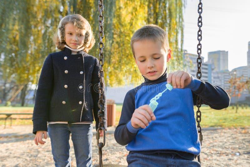 Chłopiec i dziewczynka bawiące się w jesiennym parku, dzieci siedzące na huśtawce bąbelków mydła obrazy royalty free
