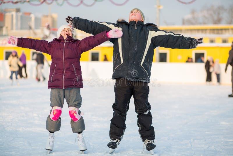 Chłopiec i dziewczyny łyżwiarstwo na lodowisku fotografia royalty free