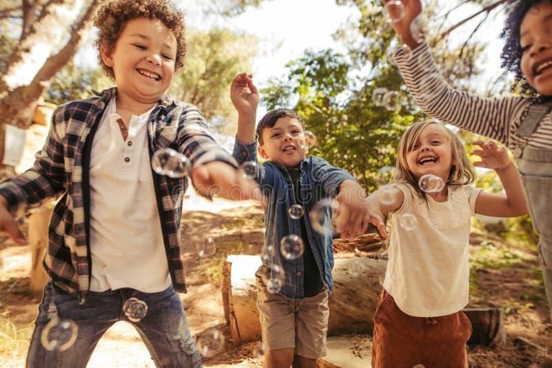 Chłopiec i dziewczyny bawić się z mydlanymi bąblami obrazy royalty free