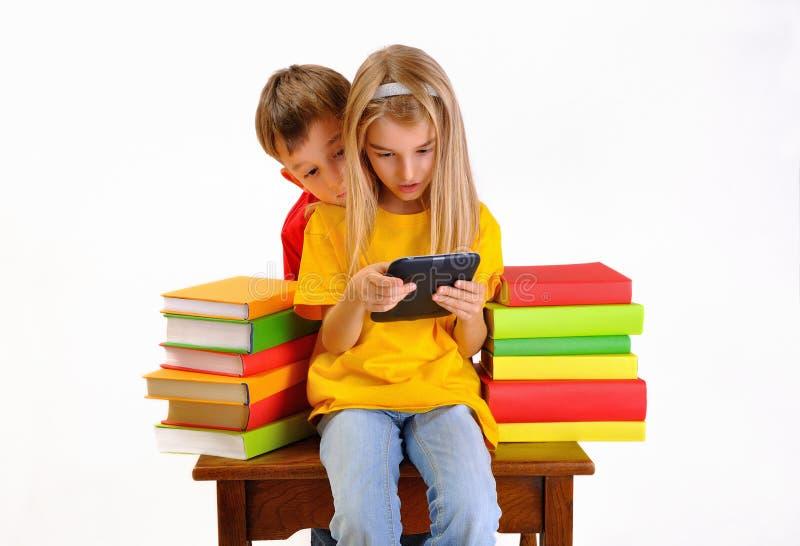 Chłopiec i dziewczyny czytelniczy ebook otaczający książkami obrazy stock