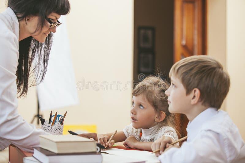 Chłopiec i dziewczyny dzieci z nauczycielem w szkole zdjęcia stock