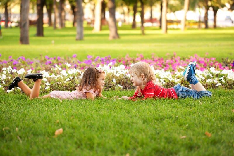 Chłopiec i dziewczyny lying on the beach na trawie fotografia stock