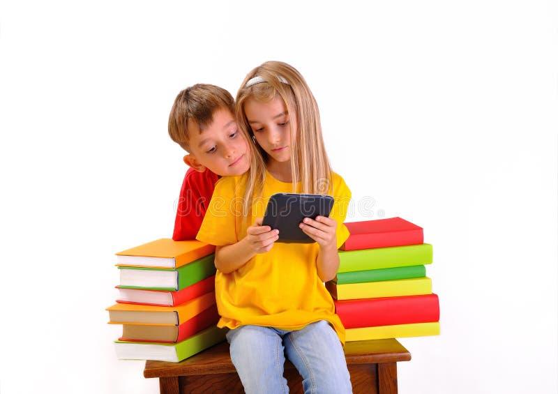 Chłopiec i dziewczyny przyglądający ebook otaczający książkami fotografia stock