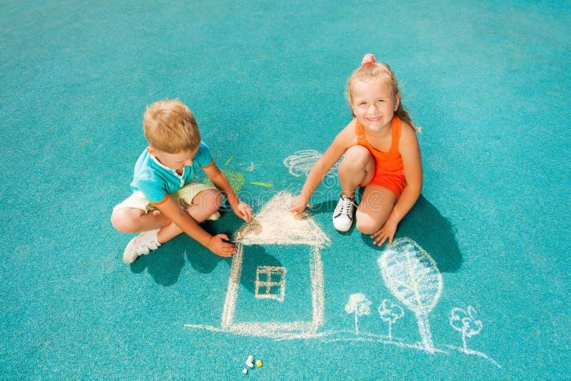 Chłopiec i dziewczyny remis pisze kredą wizerunku siedzącego toggether zdjęcia stock
