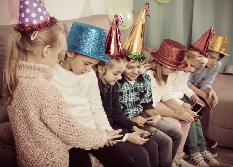 Chłopiec i dziewczyny wydaje czas bawić się z smartphones obraz royalty free