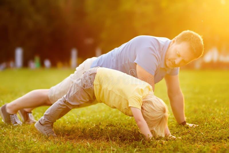 Chłopiec i jego ojciec robi deski ćwiczeniu w pogodnym lato parku obraz stock