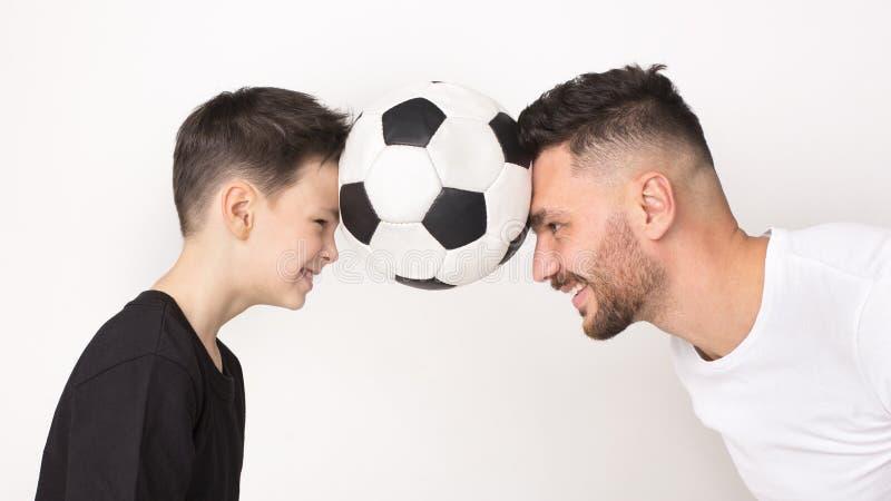 Chłopiec i jego ojciec z piłki nożnej piłką na ich głowach zdjęcia royalty free