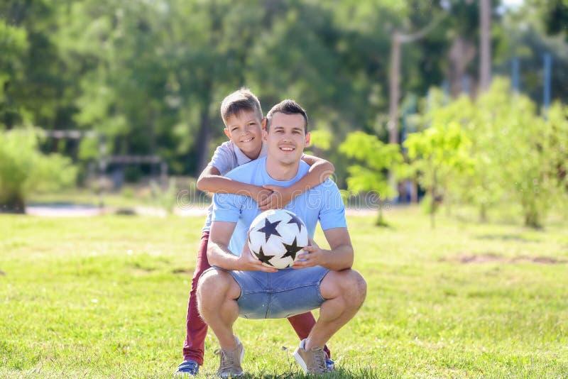 Chłopiec i jego tata z piłki nożnej piłką outdoors obraz stock