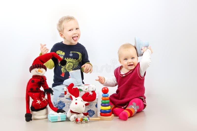 Chłopiec i mała dziewczynka bawić się z Bożenarodzeniowymi prezentami i zabawkami odizolowywającymi nad białym tłem fotografia stock