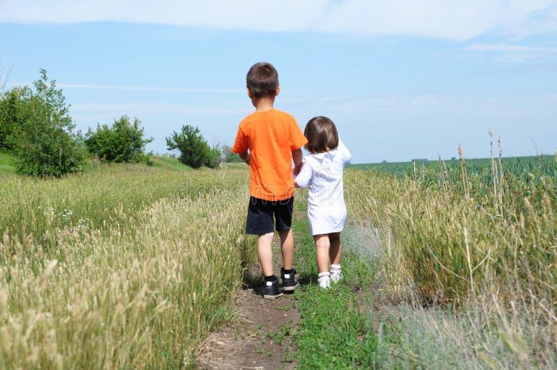 Chłopiec i mała dziewczynka chodzący na drodze w polu przy letnim dniem, bratem i siostrą daleko od, obrazy stock