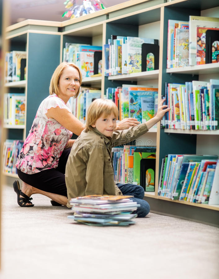 Chłopiec I nauczyciel Wybiera książki Od półka na książki zdjęcie stock