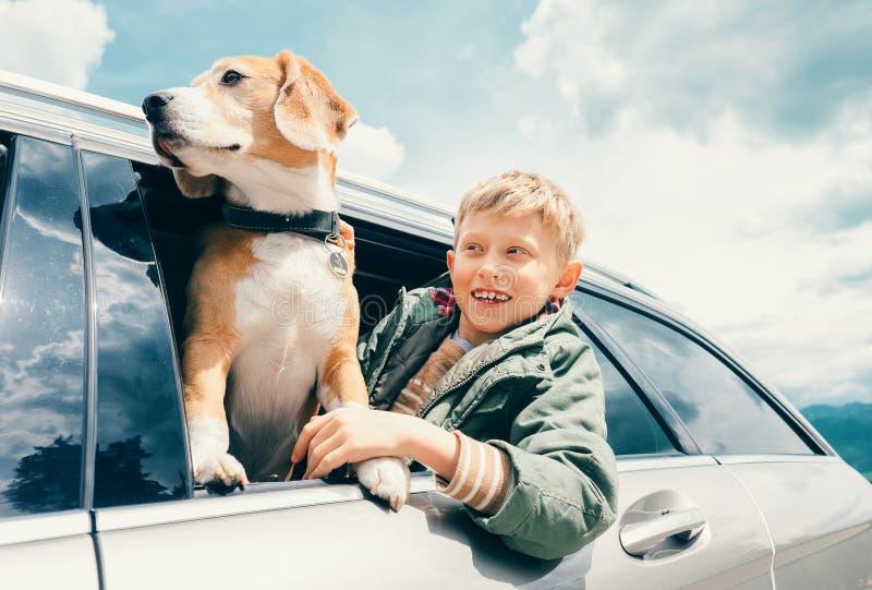 Chłopiec i pies patrzejemy out od samochodowego okno obraz royalty free
