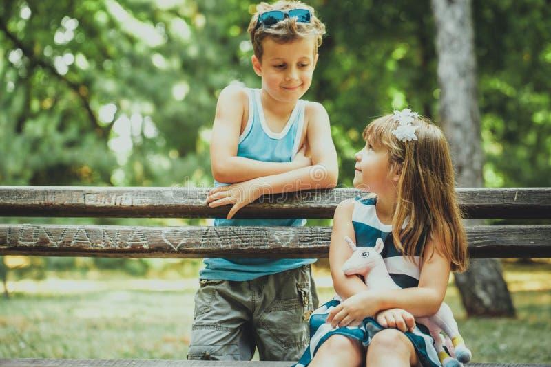 Chłopiec i szczęśliwy dziewczyny obsiadanie na ławce obrazy royalty free