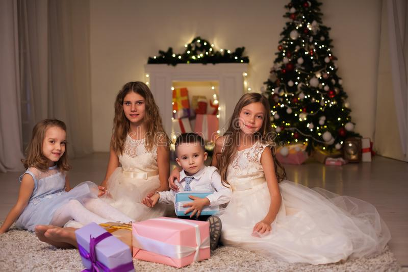 Chłopiec i trzy dziewczyna dzieciaka otwieramy Bożenarodzeniowych teraźniejszość nowego roku zimy choinki zdjęcia stock