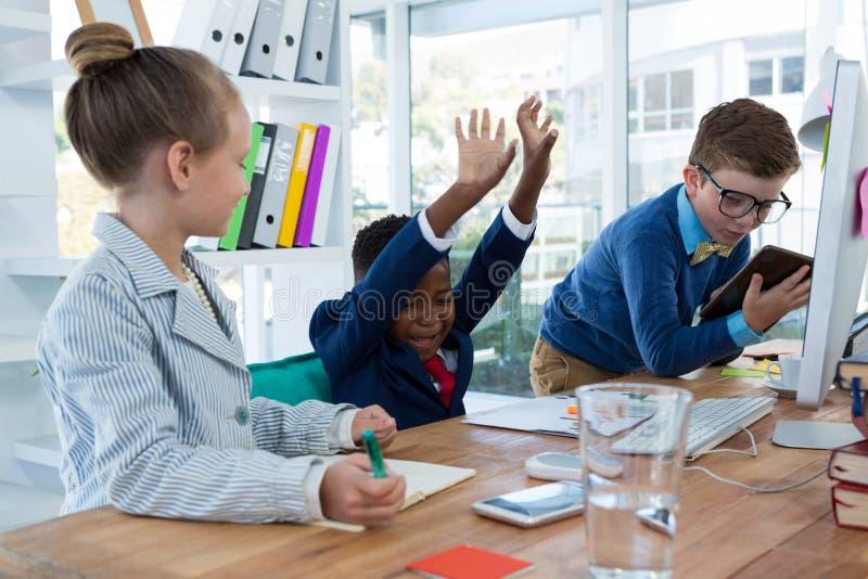 Chłopiec jako dyrektor wykonawczy śmia się podczas gdy patrzejący cyfrową pastylkę obraz royalty free