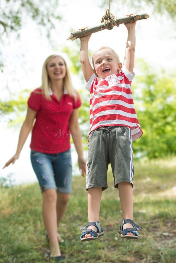 Chłopiec jazda na prowizorycznej huśtawce w drewnach Mam spojrzenia przy lotem syn troszkę fotografia royalty free