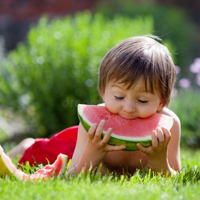 Chłopiec, je arbuza w ogródzie fotografia stock