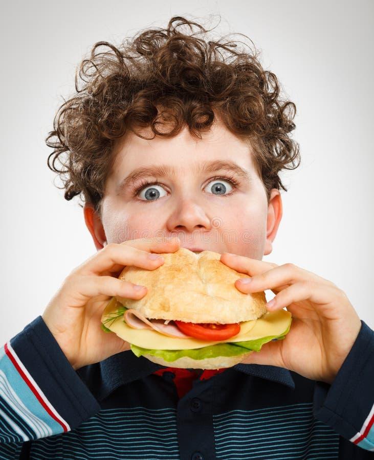 Chłopiec je dużą kanapkę obraz stock