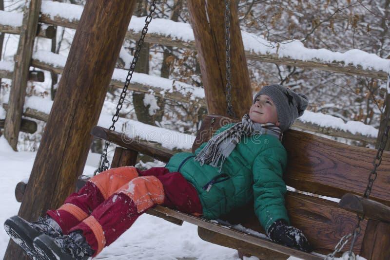 Chłopiec jedzie drewnianą huśtawkę na tle śnieżysty ogrodzenie uśmiechnięta twarz zdjęcia stock