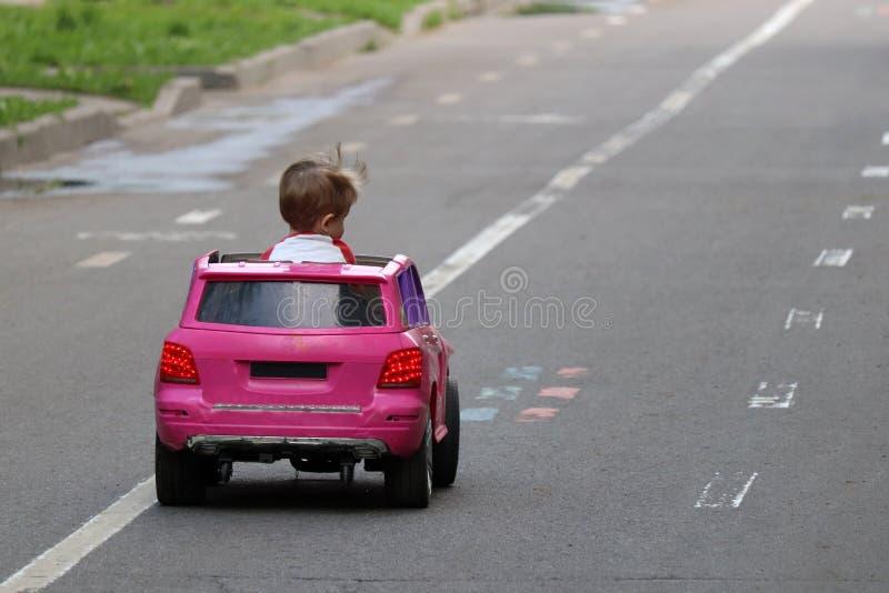 Chłopiec jedzie dużego zabawkarskiego samochód na drodze zdjęcie stock