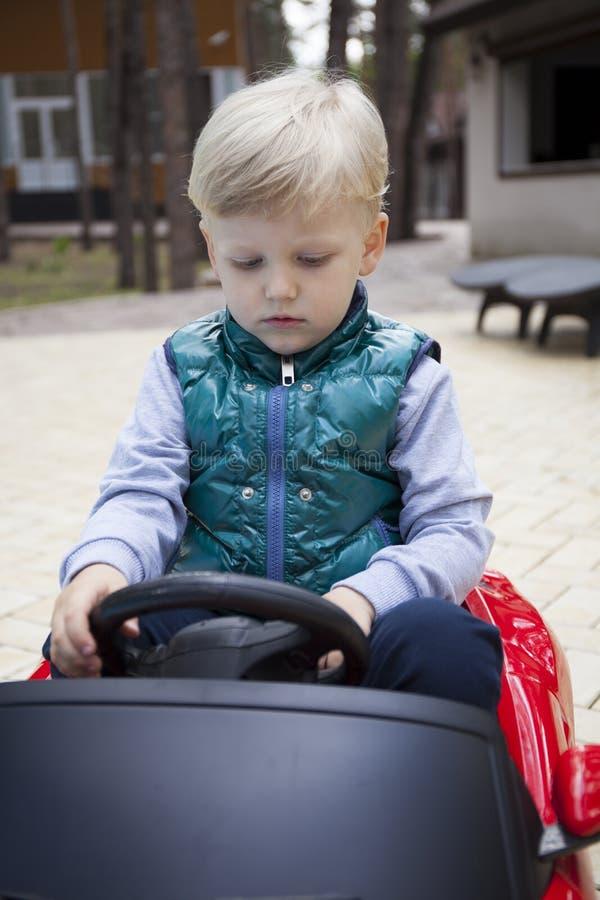 Chłopiec jedzie dużego zabawkarskiego samochód, wiosna outdoors fotografia stock