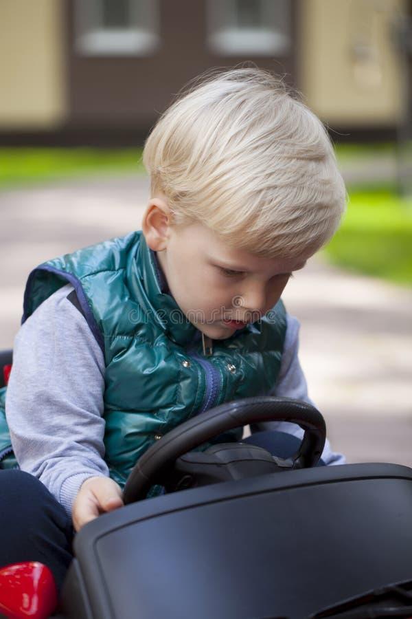 Chłopiec jedzie dużego zabawkarskiego samochód, wiosna outdoors obrazy royalty free