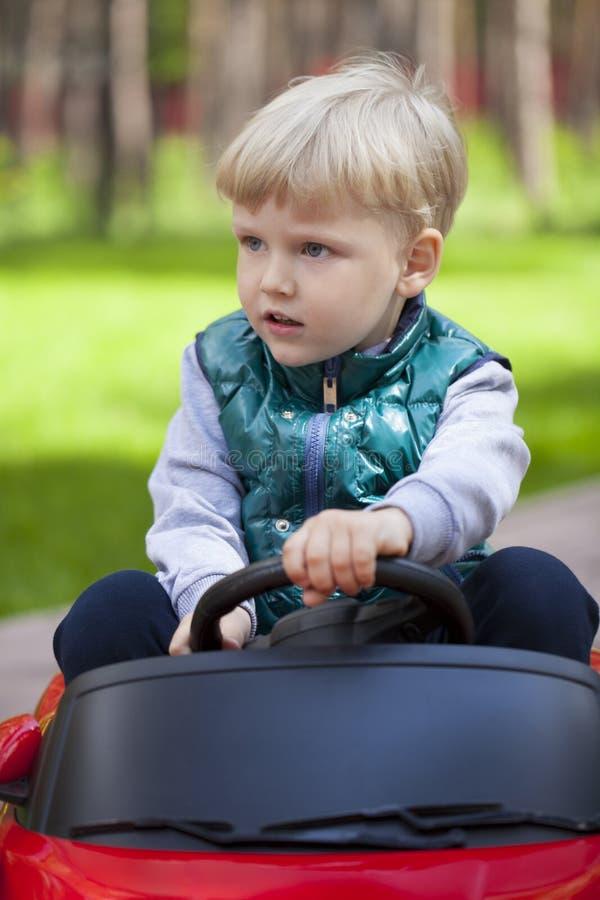 Chłopiec jedzie dużego zabawkarskiego samochód, wiosna outdoors obraz stock