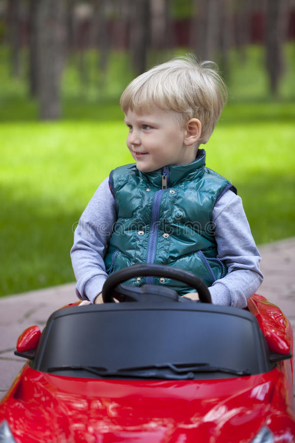 Chłopiec jedzie dużego zabawkarskiego samochód, wiosna outdoors fotografia royalty free