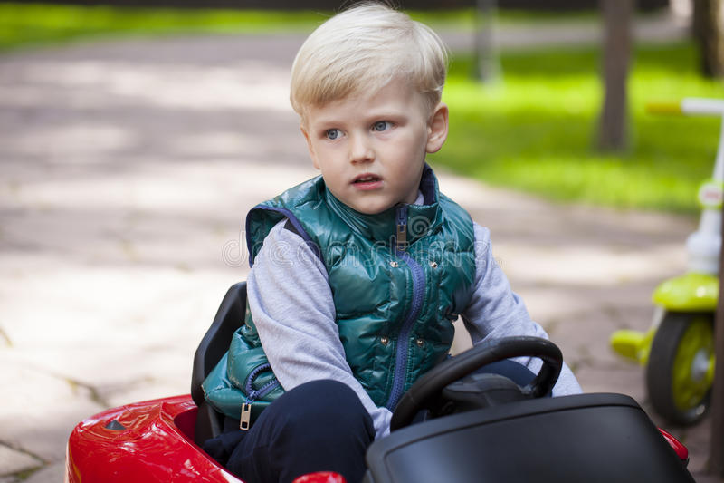 Chłopiec jedzie dużego zabawkarskiego samochód, wiosna outdoors obrazy stock