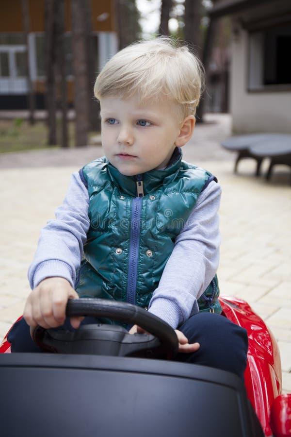 Chłopiec jedzie dużego zabawkarskiego samochód, wiosna outdoors obraz royalty free