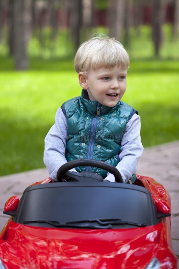 Chłopiec jedzie dużego zabawkarskiego samochód, wiosna outdoors zdjęcia stock