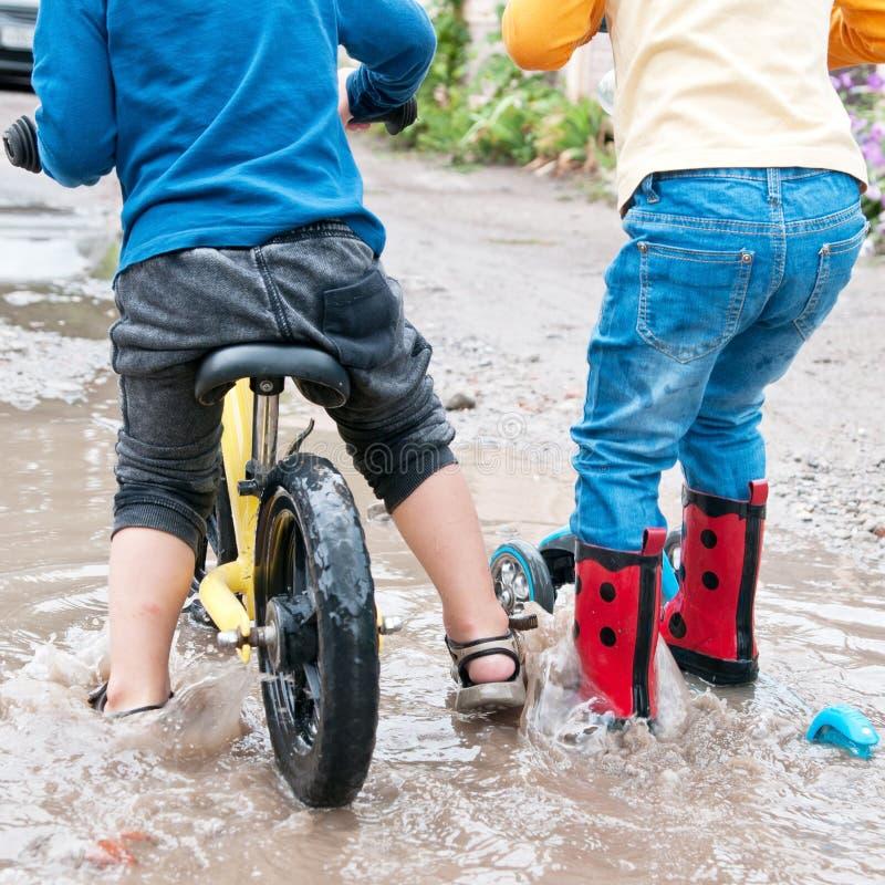 Chłopiec jedzie rower i dziewczyna jedzie hulajnoga przez głęboką kałużę obrazy stock