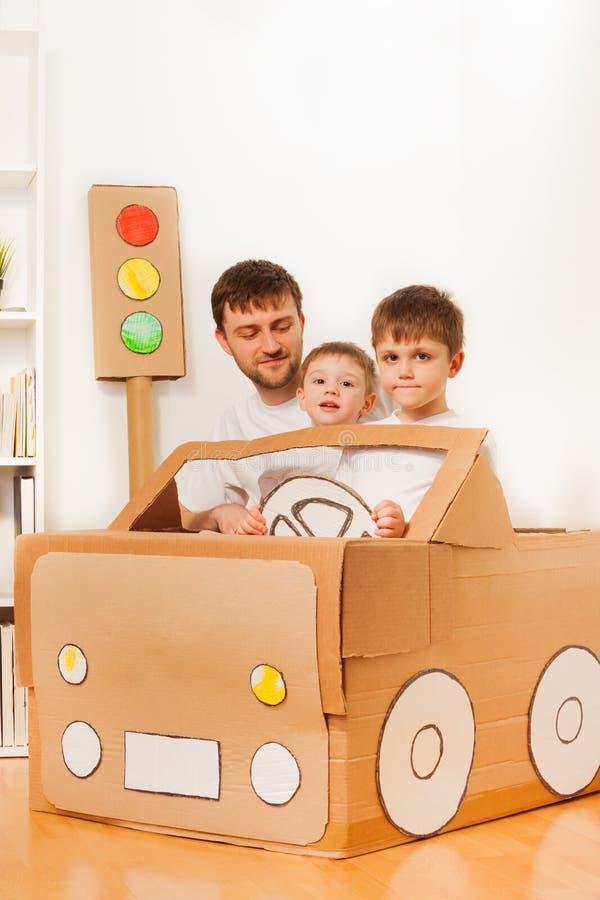 Chłopiec jedzie tata w zabawkarskim samochodzie robić karton zdjęcie royalty free