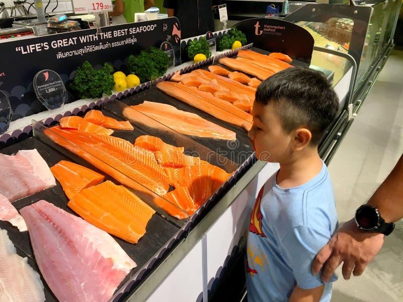 Chłopiec jest przyglądająca wiele kawałki surowa łosoś ryba dla bubla w supermarkecie Tajlandia Bangkok, Grudzień 22, 2018 fotografia stock