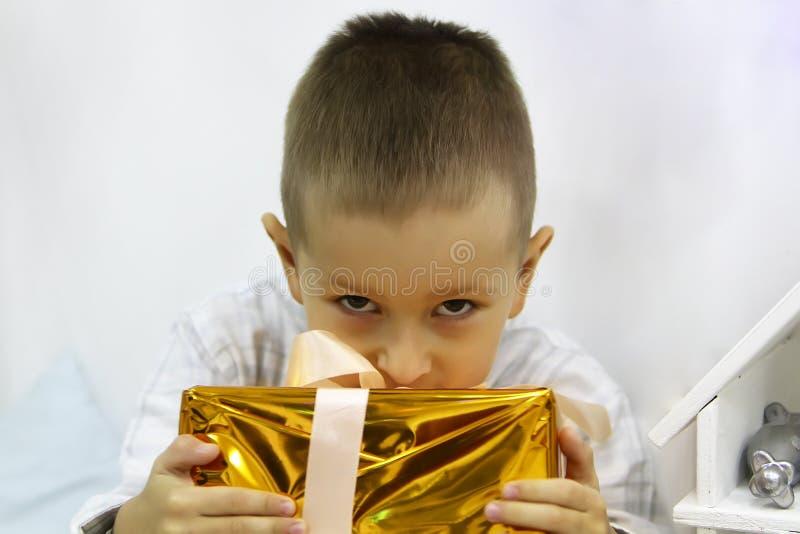 Chłopiec jest siedząca jego prezent i ściskająca fotografia stock