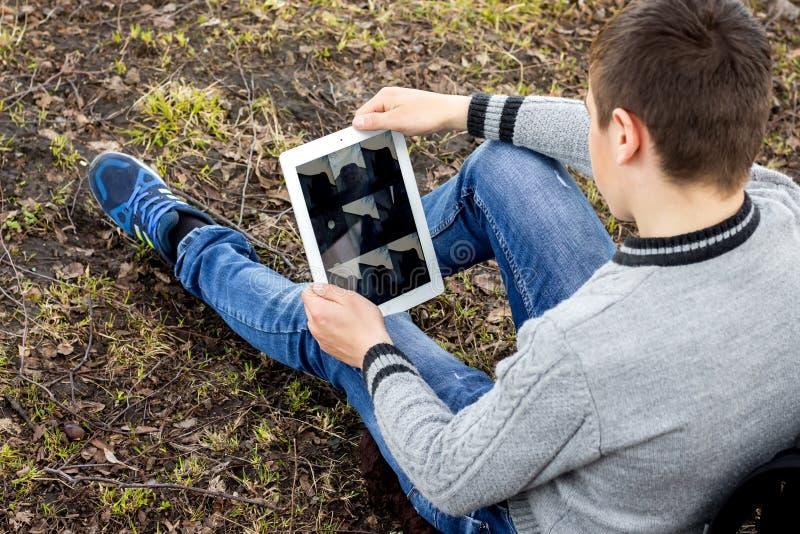 Chłopiec jest siedząca na trawie i patrzeć pastylkę Nowożytny technolo zdjęcia stock
