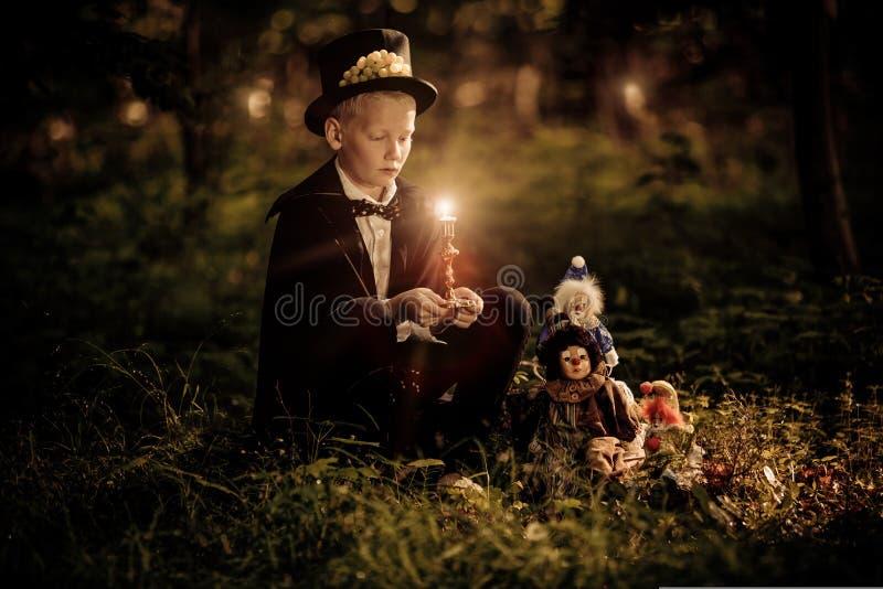 Chłopiec jest ubranym łęku krawat i odgórnego kapelusz trzyma świeczkę fotografia royalty free