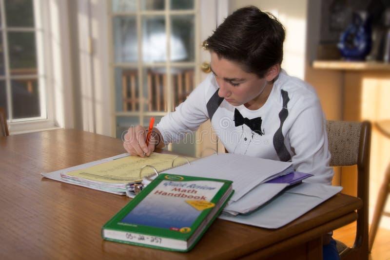 Chłopiec jest ubranym białą koszula robi jego matematyki pracie domowej obrazy royalty free
