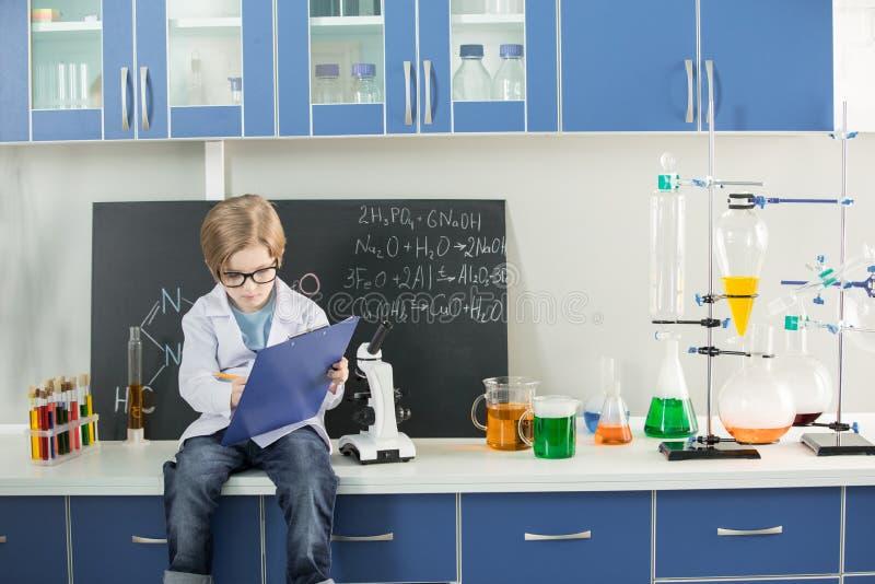 Chłopiec jest ubranym lab żakiet robi notatkom w schowku w nauki laboratorium obrazy royalty free