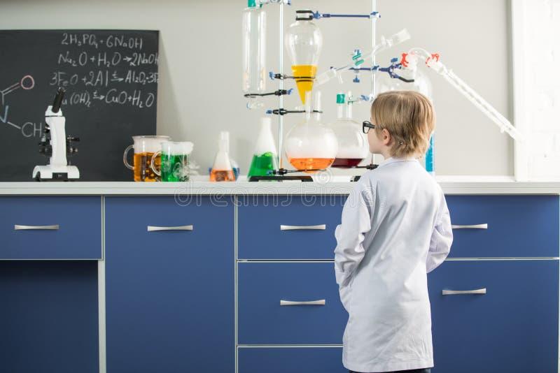 Chłopiec jest ubranym lab żakiet w nauki laboratorium obrazy stock