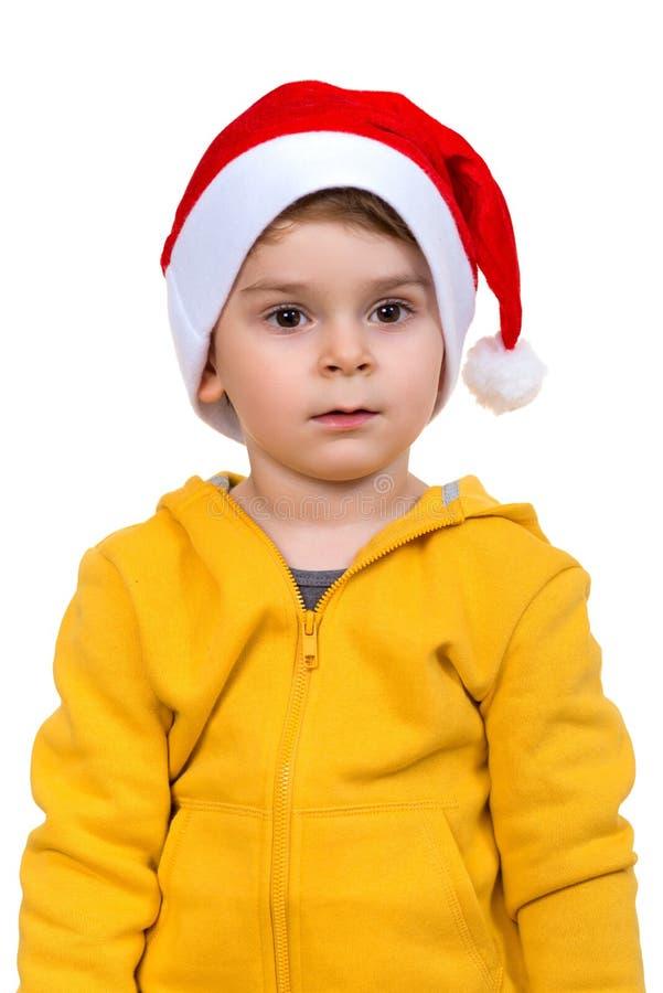 Chłopiec jest ubranym na czerwonym Santa pomagiera kapeluszu Odizolowywający nad białym tłem obraz stock