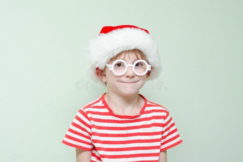 Chłopiec jest ubranym szkła i Święty Mikołaj kapeluszu stojaki na backgrou zdjęcia royalty free